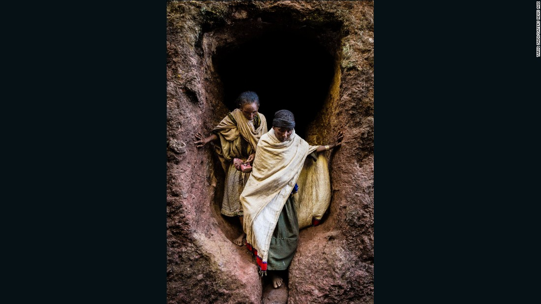 Two pilgrims emerge from a tunnel in one of Lalibela's stone churches.