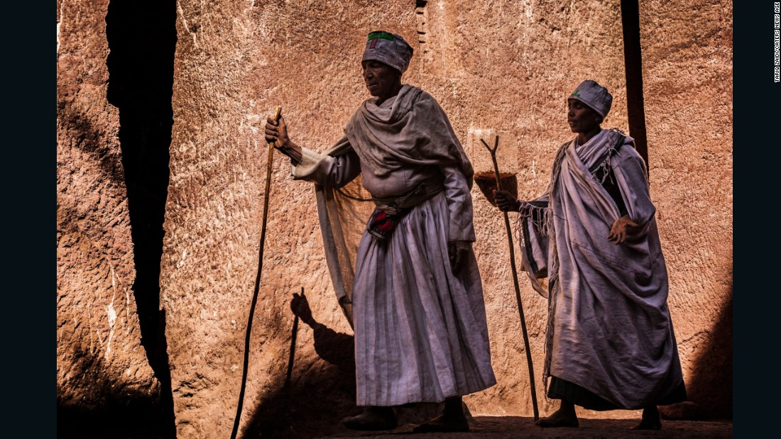 In Lalibela life feels largely untouched by the centuries. Two priests, wrapped in devotional white robes and carrying prayer staffs.