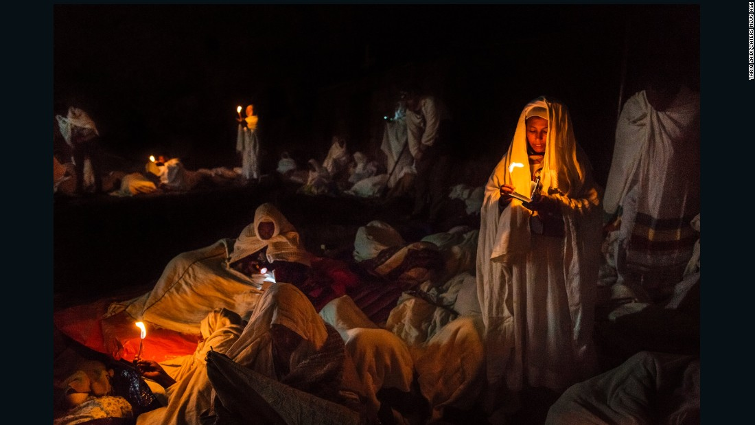 A group of pilgrims pray and read their bibles by candlelight around the churches. During the great feasts of the Ethiopian Orthodox calendar, such as Christmas Eve, all-night ceremonies can last up to 20 hours and many thousands of pilgrims, who have traveled here from all over the country, camp outside to be close to the action.