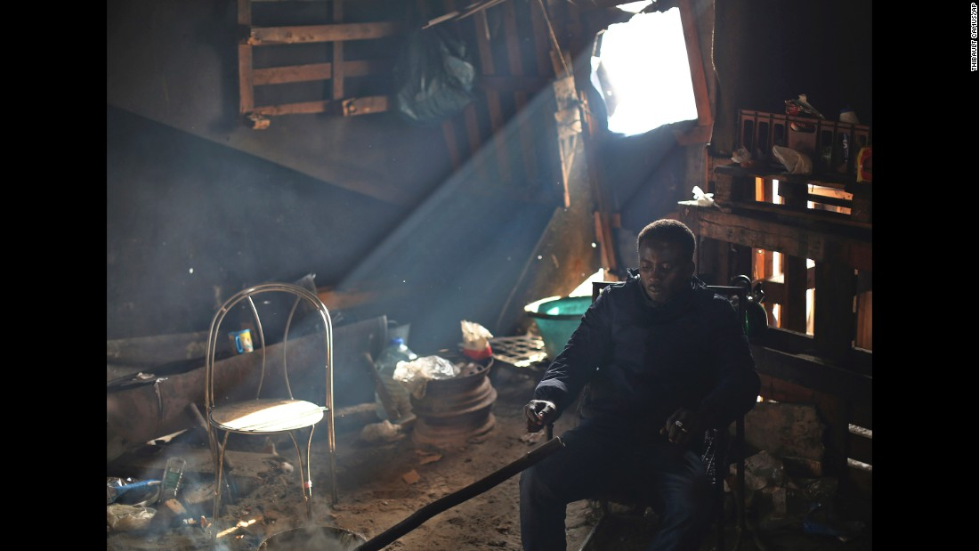 A migrant man sits inside a shack that remains in the otherwise demolished Jungle camp on October 27. French authorities said Wednesday that almost 5,600 migrants had been bused to relocation centers around France.