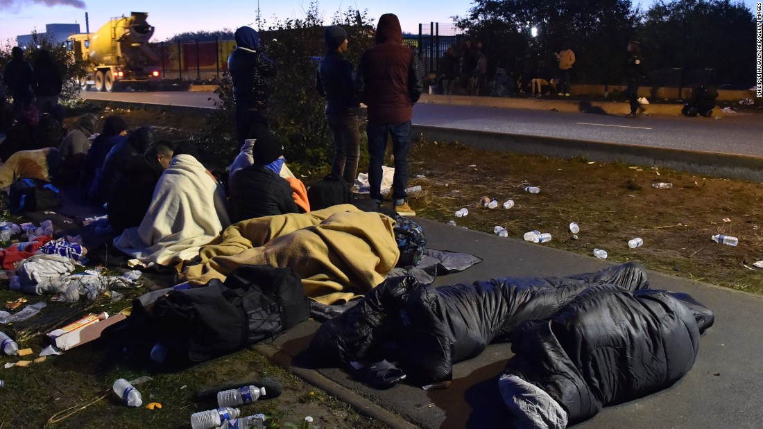 A group of migrants who slept outside an aid station near the Jungle wait to be assigned relocation to processing centers across France on October 27.