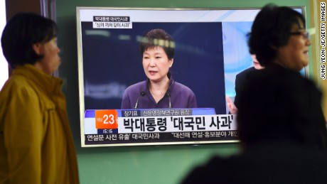 People walk past a television screen showing South Korean President Park Geun-Hye making a public apology on October 25.