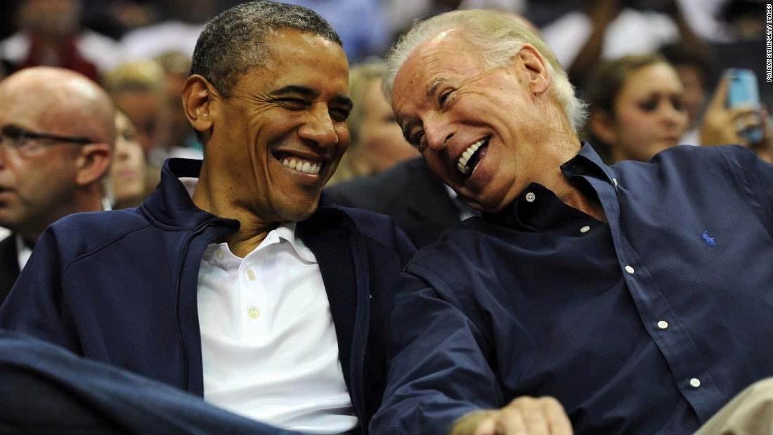 Obama and Biden laugh together as they attend a U.S. basketball game in July 2012.