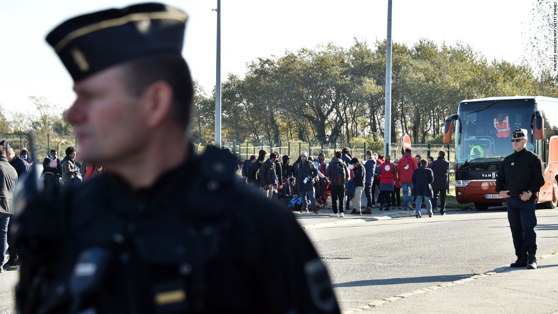 "French authorities stand by as migrant minors board a bus to relocation centers on October 28. Authorities began work on Monday to clear the infamous migrant camp known as the Calais ""Jungle"" in northern France."