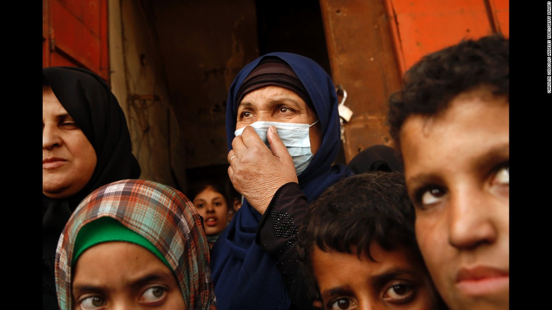 A woman wears a mask to alleviate her difficulty breathing due to the contaminated air in Qayyara on October 26.