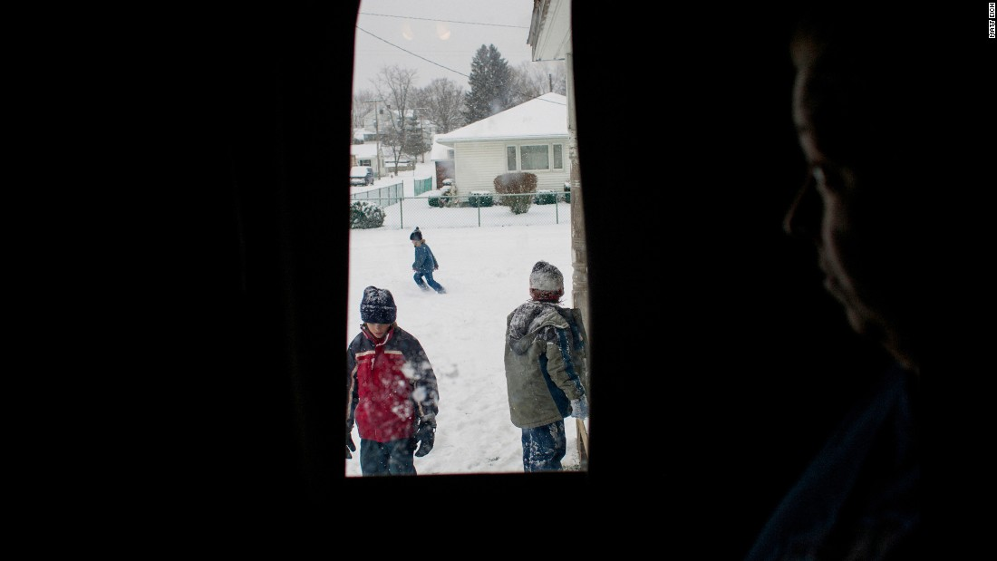 "Tracy Sellers watches her kids play with neighbors in the front yard of their home in Chauncey, Ohio, in 2007. Chauncey's coal-mining corporations fled, leaving the community impoverished and ""brokenhearted,"" according to Eich."