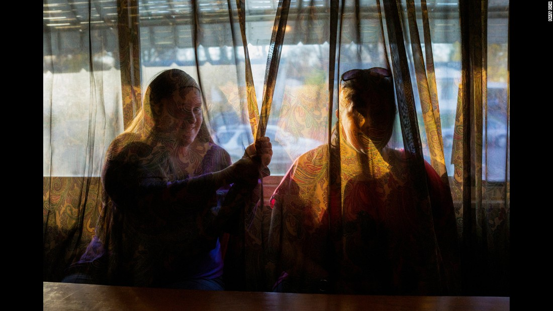 The twins are seen behind a living-room curtain in 2015.