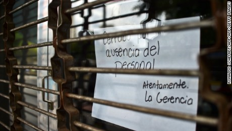 "A closed store shows a sign which reads ""closed for lack of staff"" in Caracas, on October 28, 2016.  Venezuela's opposition sought to pressure President Nicolas Maduro on Friday with a strike, which he threatened to break with army takeovers of paralyzed firms. The strike risks exacerbating the shortages of food and goods gripping the country, but it seemed to be only partially observed on Friday morning.  / AFP / RONALDO SCHEMIDT        (Photo credit should read RONALDO SCHEMIDT/AFP/Getty Images)"