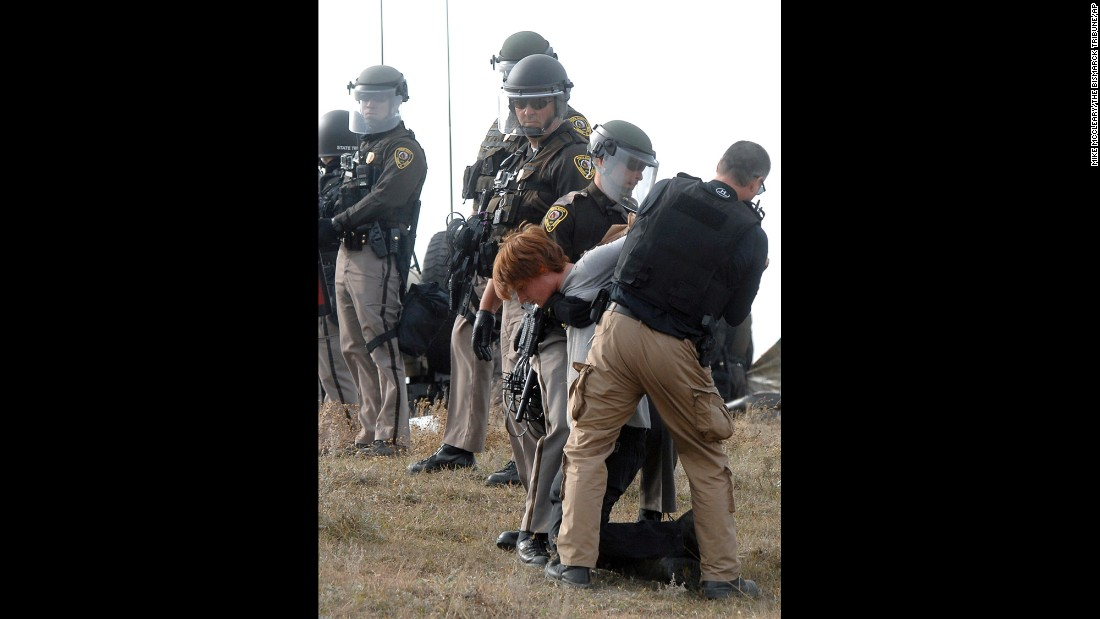 A protester is arrested as law enforcement surrounds the camp on October 27.