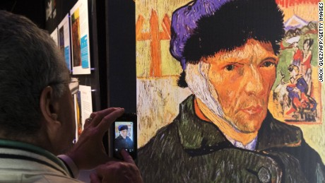 A visitor takes pictures of the art exhibition 'Van Gogh Alive' in Tel Aviv. Self-Portrait with Bandaged Ear by Dutch artist Vincent Van Gogh.