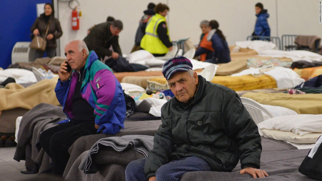 Residents from the village of Caldarola prepare to spend the night in an emergency camp set up in a warehouse on October 30.