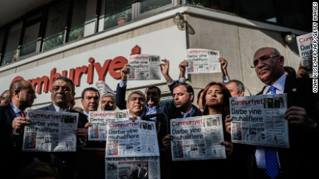 Main opposition Republic People's Party (CHP) members of parliament Sezgin Tanrikulu (L), Baris Yarkadas (C), Mahmut Tanal (R) and politicians hold today's copy of Cumhuriyet newspaper in front of the newspaper's headquarters on October 31, 2016 in Istanbul during a police operation. Turkish police detained the editor-in-chief of the opposition newspaper Cumhuriyet, state media reported on October 31, while the daily said several of its writers were taken into police custody. Murat Sabuncu was detained while authorities searched for executive board chairman Akin Atalay and writer Guray Oz, the official news agency Anadolu said. The cover reads : 'Coup against opposition'. / AFP / OZAN KOSE (Photo credit should read OZAN KOSE/AFP/Getty Images)