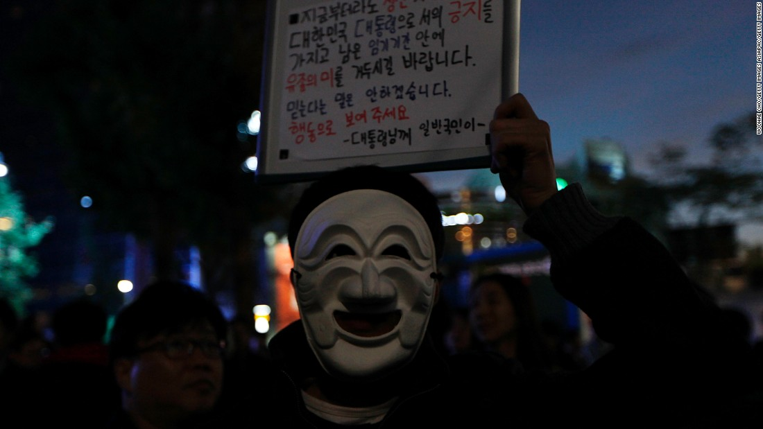 "A protester wearing a traditional Korean mask holds a placard saying ""You Need to Resign Now"" during the protest."