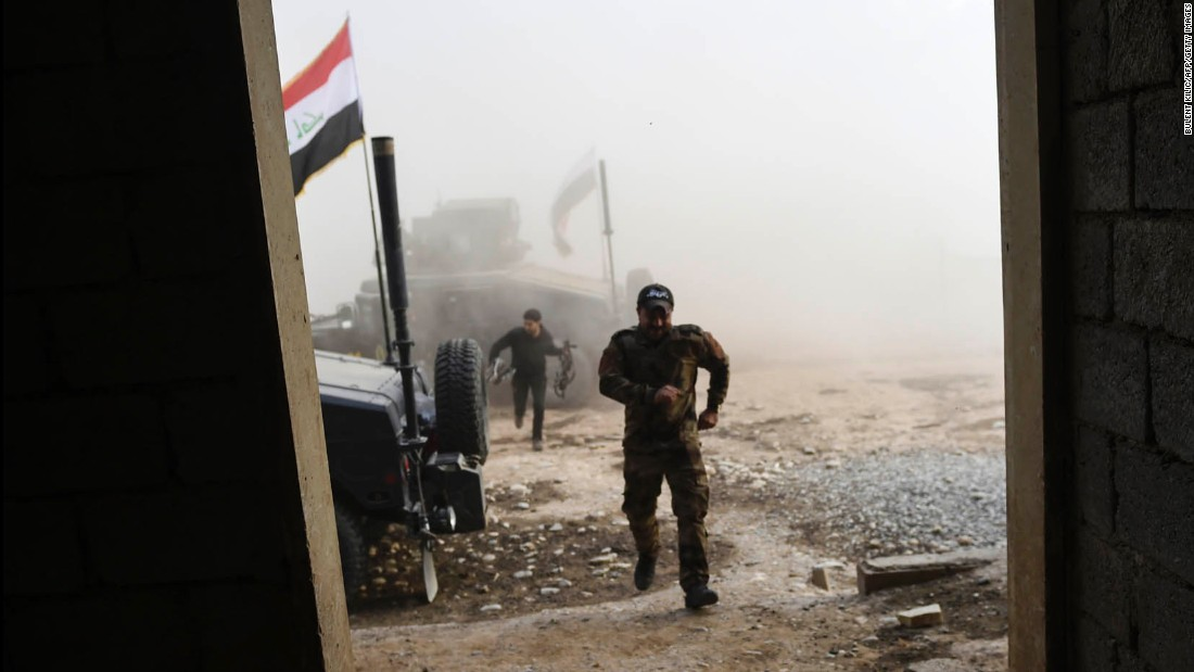 Iraqi forces run for cover after a mortar shell struck near the village of Bazwaya on Monday, October 31.