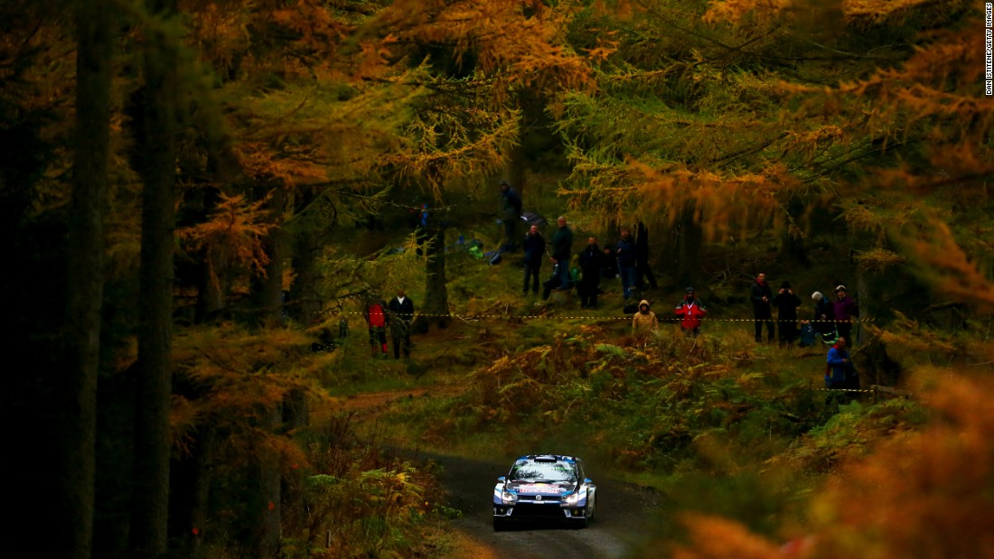 The rally car of Sebastien Ogier and Julien Ingrassia speeds through a forest in Mynydd Hiraethog, Wales, on Thursday, October 27.