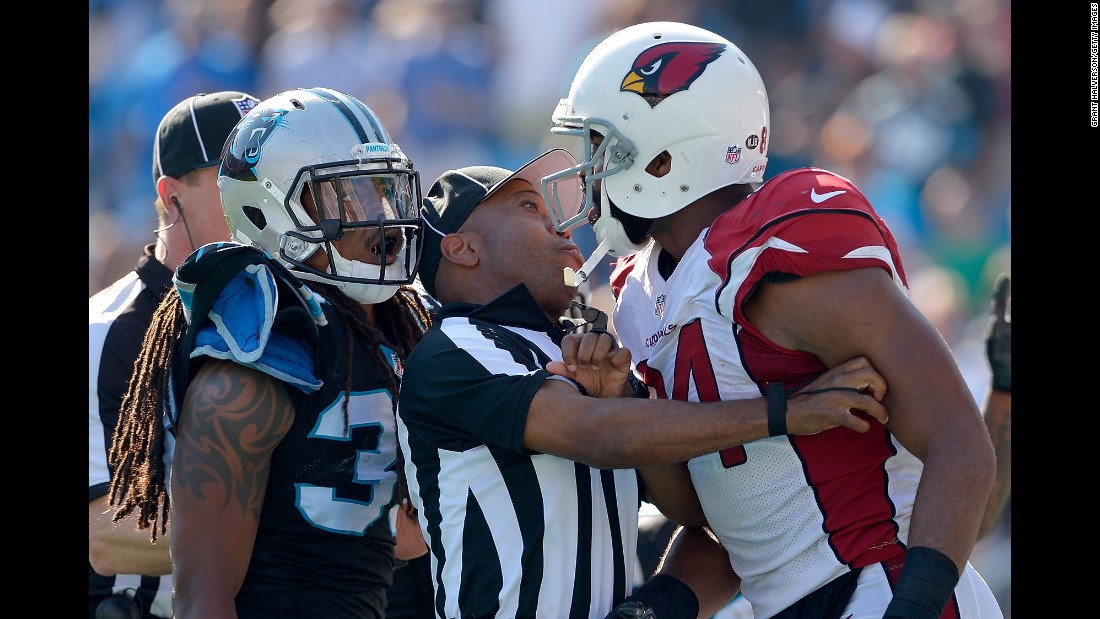 An official stands between Carolina's Tre Boston, left, and Arizona's Jermaine Gresham during an NFL game in Charlotte, North Carolina, on Sunday, October 30.