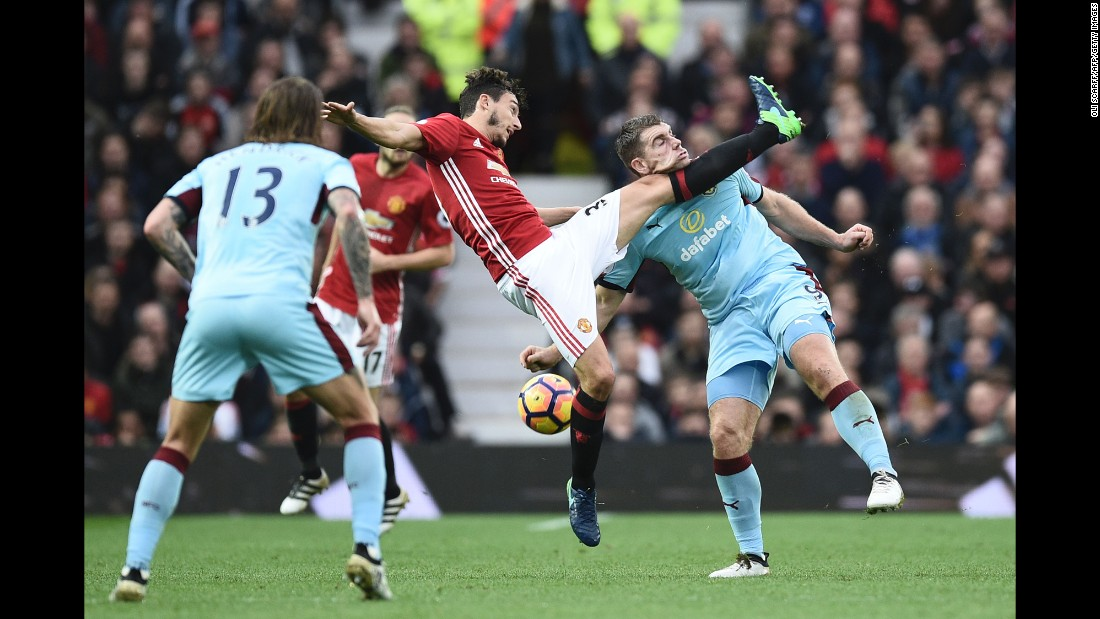 The leg of Manchester United defender Matteo Darmian catches the chin of Burnley forward Sam Vokes during a Premier League match in Manchester, England, on Saturday, October 29.