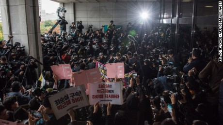 Reporters and protesters surround Choi Soon-sil as she enters the prosecutor's office Monday in Seoul.