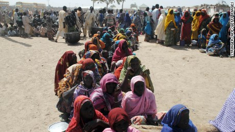 Women and children sit among displaced people waiting to be served food at Dikwa Camp, in Borno State, Nigeria, in January, 2016.