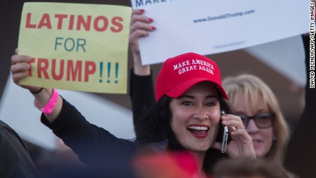 A woman hoods a sign expressing Latino support for Republican presidential candidate Donald Trump at his campaign rally at the Orange County Fair and Event Center, April 28, 2016, in Costa Mesa, California. Trump is vying for votes in the June 7 California primary election in hope of narrowing the gap to the 1,237 delegates needed to win the Republican presidential nomination.