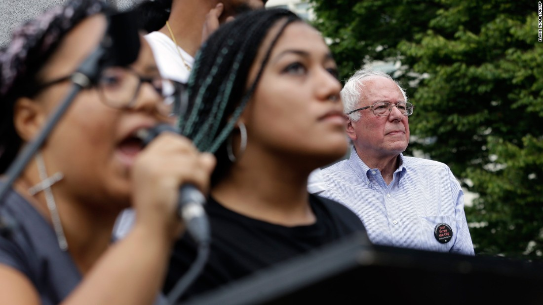 "Seconds after Sanders took the stage for a rally in Seattle, a dozen protesters from the city's Black Lives Matter chapter <a href=""http://www.cnn.com/2015/08/08/politics/bernie-sanders-black-lives-matter-protesters/"" target=""_blank"">jumped barricades and grabbed the microphone</a> on August 8, 2015. Holding a banner that said ""Smash Racism,"" two of the protesters -- Marissa Johnson, left, and Mara Jacqueline Willaford -- addressed the crowd. Sanders stood just feet away off stage, chatting with his wife and the three aides that came to Seattle with him. His aides said the senator had no plans of leaving during the protests, but once Johnson did not appear willing to give up the mic after a moment of silence, organizers effectively shut down the event. Sanders never addressed the crowd, but he did make his way through it to shake hands and take pictures."