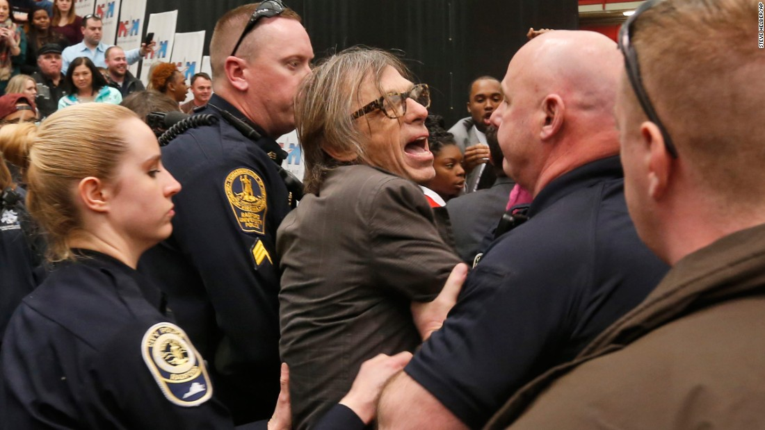 "Christopher Morris, a photographer on assignment for Time magazine, is escorted by police during a Trump rally in Radford, Virginia, on February 29, 2016. Morris said a Secret Service agent choked him and slammed him to the ground as he tried to leave a media pen at the event. <a href=""http://www.cnn.com/2016/02/29/politics/donald-trump-event-protest-rally/"" target=""_blank"">The incident was caught on video.</a>"