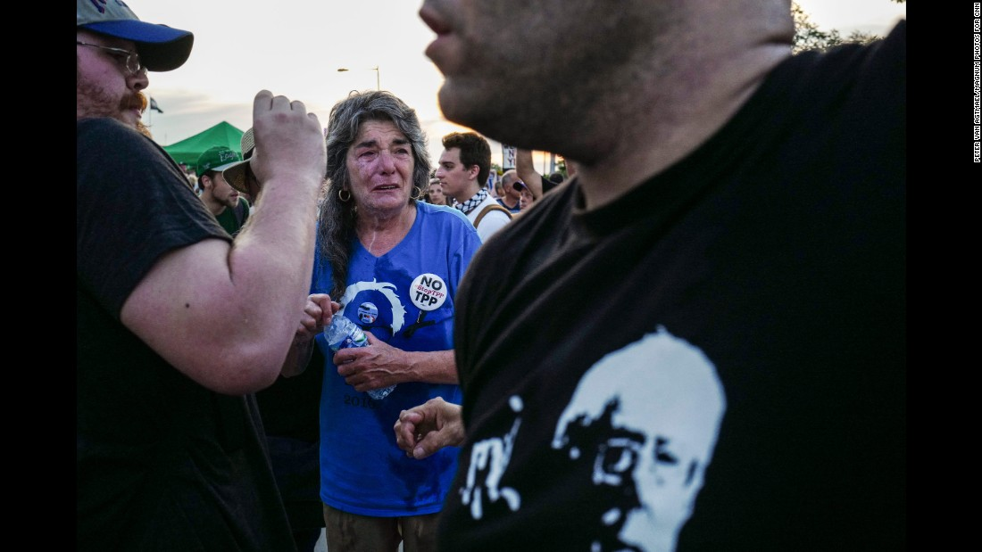 A woman reacts after allegedly being pepper-sprayed as a group of protesters tried to push through the police lines and enter the Democratic National Convention.