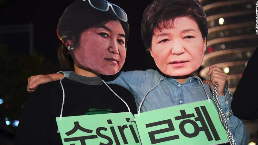 Protesters wear masks depicting Choi Soon-sil and Park Geun-hye.