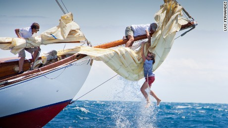 The bow woman of the yacht Gipsy loses her balance following a wave but recovers thanks to a crew member to climb back on board during the Puig Vela Classica Barcelona, as taken by Luis Fernandez.