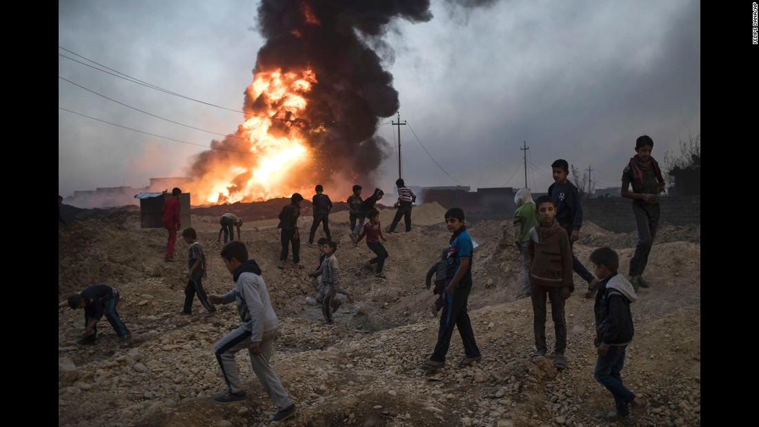 Children play near a burning oil field in Qayyara, south of Mosul, on November 3.