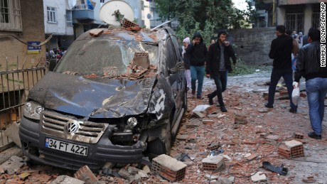 People walk through the debris from an explosion in the southeastern Turkish city of Diyarbakir early Friday, Nov. 4, 2016. A large explosion hit Diyarbakir, the largest city in Turkey's mainly Kurdish southeast region on Friday, wounding several people, the state-run Anadolu Agency reported. The cause of the explosion was not immediately known but local media said it may have been caused by a car bomb. Turkish authorities have imposed a temporary blackout on coverage of the blast citing public order and national security reasons. (AP Photo/Mahmut Bozarslan)