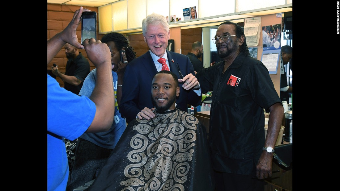 Former US President Bill Clinton pretends to cut D.J. Anderson's hair as he visits a Las Vegas barbershop on Thursday, November 3. Clinton was campaigning for his wife.