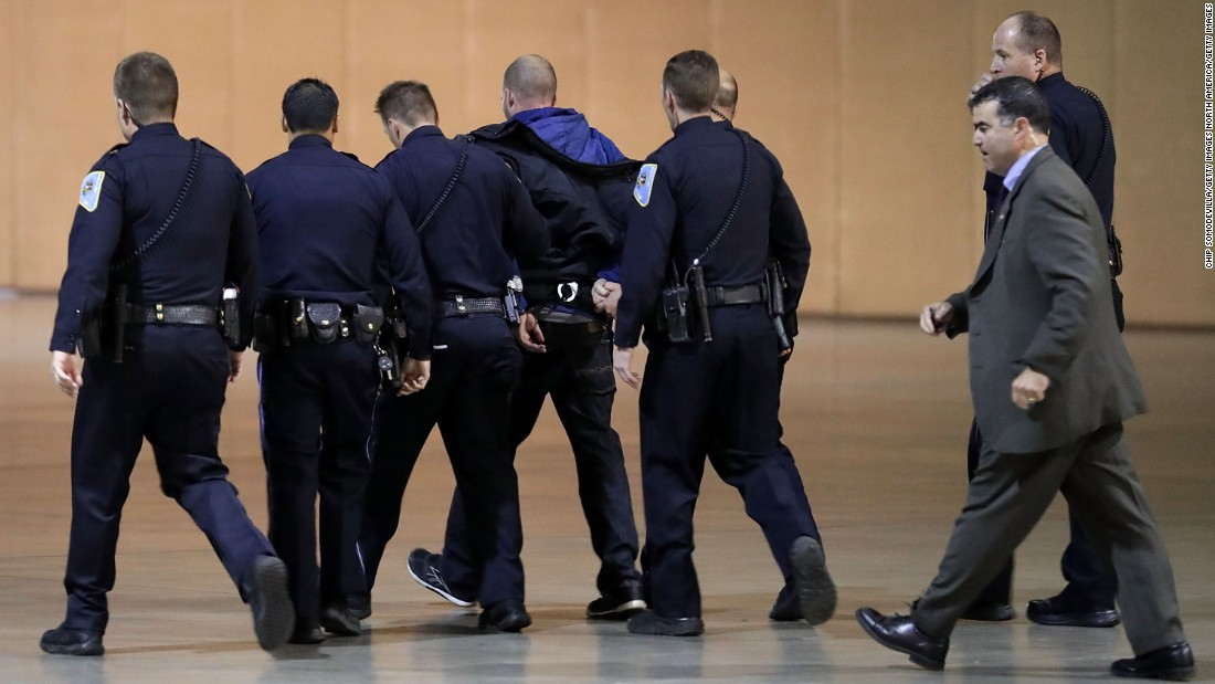 Police officers and Secret Service agents take a man away in handcuffs after the Reno disruption.