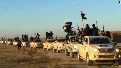 ISIS militants ride through Raqqa, Syria.