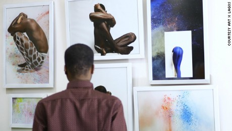 "A visitor examines Nigerian fashion designer Maki Oh and artist Lakin Ogunbanwo's exhibition of  the Nigerian expression ""ehn"". The term can mean many things, here they explore it's use as a question - ""ehn?"""