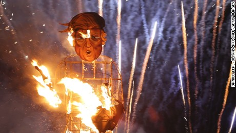 "Fireworks explode as flames engulf an effigy of US presidential candidate Donald Trump while it is burned as the ""Celebrity Guy"" at the Edenbridge Bonfire Society bonfire night in Edenbridge, south of London, on November 5, 2016. The giant effigy of US presidential candidate Donald Trump wielding the head of rival Hillary Clinton went up in flames during the traditional British bonfire celebrations at Edenbridge south of London. The 36-foot (11-metre) high model of Trump dressed in shorts decorated with images of Mexicans was packed with fireworks and set alight as part of the annual Bonfire Night celebrations.  / AFP / DANIEL LEAL-OLIVAS        (Photo credit should read DANIEL LEAL-OLIVAS/AFP/Getty Images)"