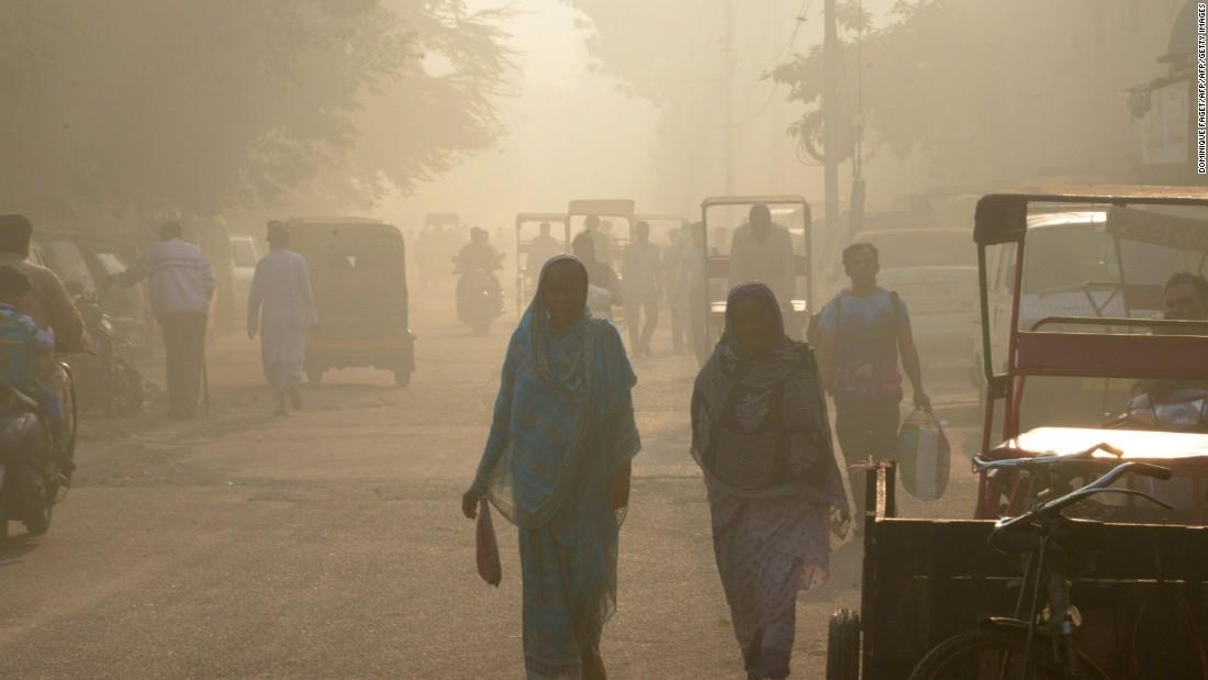 Indian commuters walk through the smog in the old quarters of New Delhi.