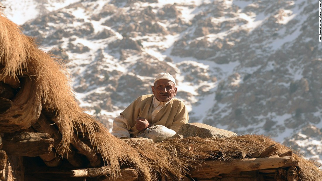 A Moroccan man sits on the roof of his house. Ski tours often stay in refuges in the mountains; basic shelters with bunk beds and maybe a hearth from where parties can explore each day.