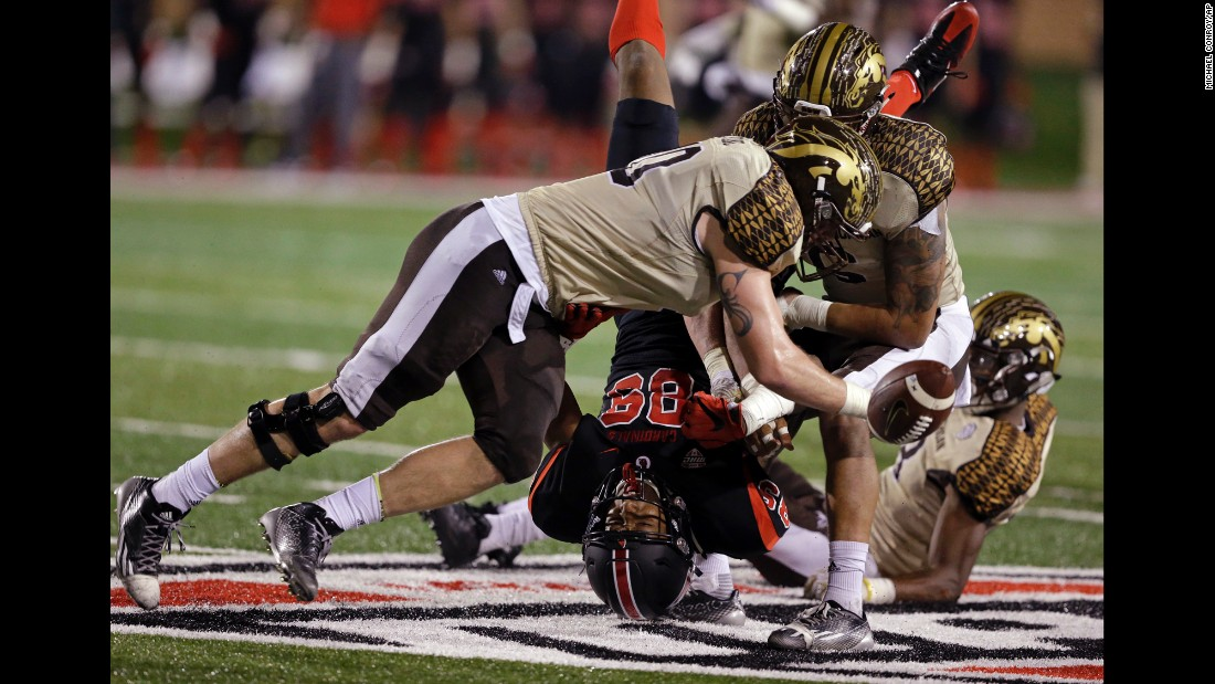 Ball State wide receiver Damon Hazelton Jr. fumbles the ball as he's hit by Western Michigan players in Muncie, Indiana, on Tuesday, November 1.