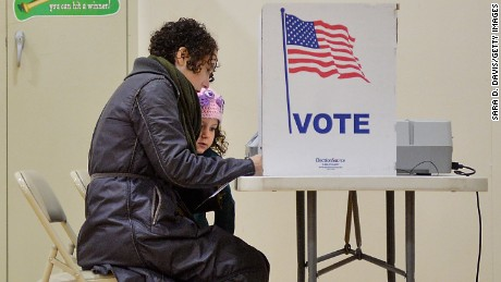 Willa Domina, 6, watches her mother, Emily Katz, votes at a polling station on November 8, 2016 in Durham, North Carolina. Schools serving as voting precincts closed across the county in preparation of crowded parking lots and possible violence as the nation goes to the polls to vote for the next president.