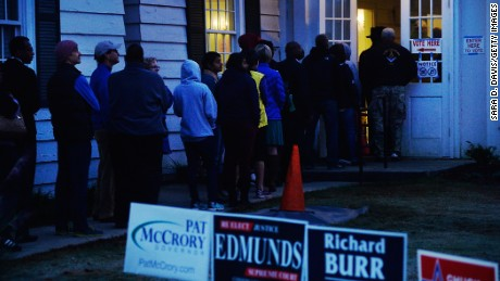 Early morning voters try to make their way inside a voting precinct to get out of the cold temperatures on November 8, 2016 in Durham, North Carolina.