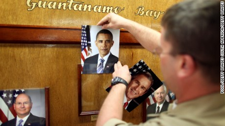GUANTANAMO BAY, CUBA - JANUARY 20:  (NOTE TO EDITORS: PHOTO HAS BEEN REVIEWED BY US MILITARY OFFICIALS) U.S. Navy Chief Petty Officer Bill Mesta replaces an official picture of outgoing President George W. Bush with that of newly- sworn-in U.S. President Barack Obama, in the lobby of the headquarters of the U.S. Naval Base January 20, 2009 in Guantanamo Bay, Cuba.  Bush's eight-year presidency, which has overseen the detention of prisoners at Guantanamo and elsewhere, concluded midday today, and President Barack Obama has said he intends to close the offshore prison and move the trials to U.S. courts. (Photo by Brennan Linsley-Pool/Getty Images)