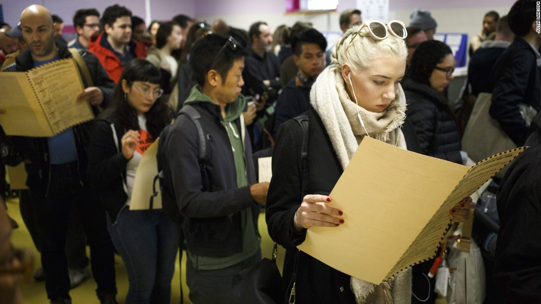 A woman reads over a ballot while waiting to vote in Brooklyn.