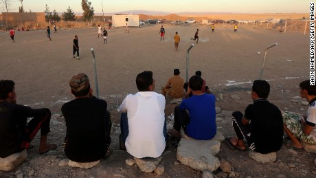"""Young Iraqi men who fled the violence in the northern city of Tal Afar watch as others play football at the Bahrka camp for internally displaced people, some ten kilometres west of Arbil, in the autonomous Kurdistan region, on September 2, 2015. More than 13 million children are being denied an education by Middle East conflicts, the UN said im a report, warning """"the hopes of a generation"""" would be dashed if they cannot return to classrooms. AFP PHOTO / SAFIN HAMED        (Photo credit should read SAFIN HAMED/AFP/Getty Images)"""