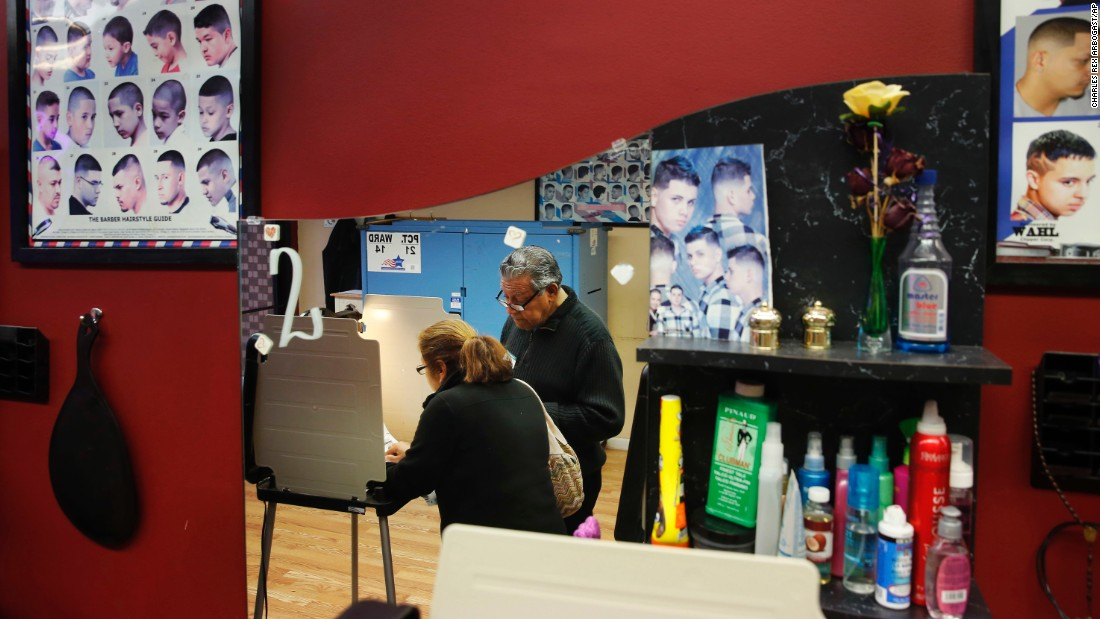 Democratic polling judge John Ramirez is reflected in a mirror as he helps a voter at a beauty salon in Chicago.