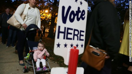 ALEXANDRIA, VA - NOVEMBER 08:  Local resident Kendra Isaacson (L) waits in-line with her 11-month-old daughter Katie Isaacson for casting her ballot outside a polling place on Election Day November 8, 2016 in Alexandria, Virginia. Americans across the nation are picking their choice for the next president of the United States.  (Photo by Alex Wong/Getty Images)