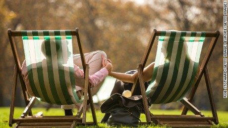 LONDON, ENGLAND - OCTOBER 31:  A couple relax in the sunshine in Green Park on October 31, 2014 in London, England.  Temperatures in London are forecasted to exceed 20 degrees making today the hottest Halloween on record.  (Photo by Rob Stothard/Getty Images)