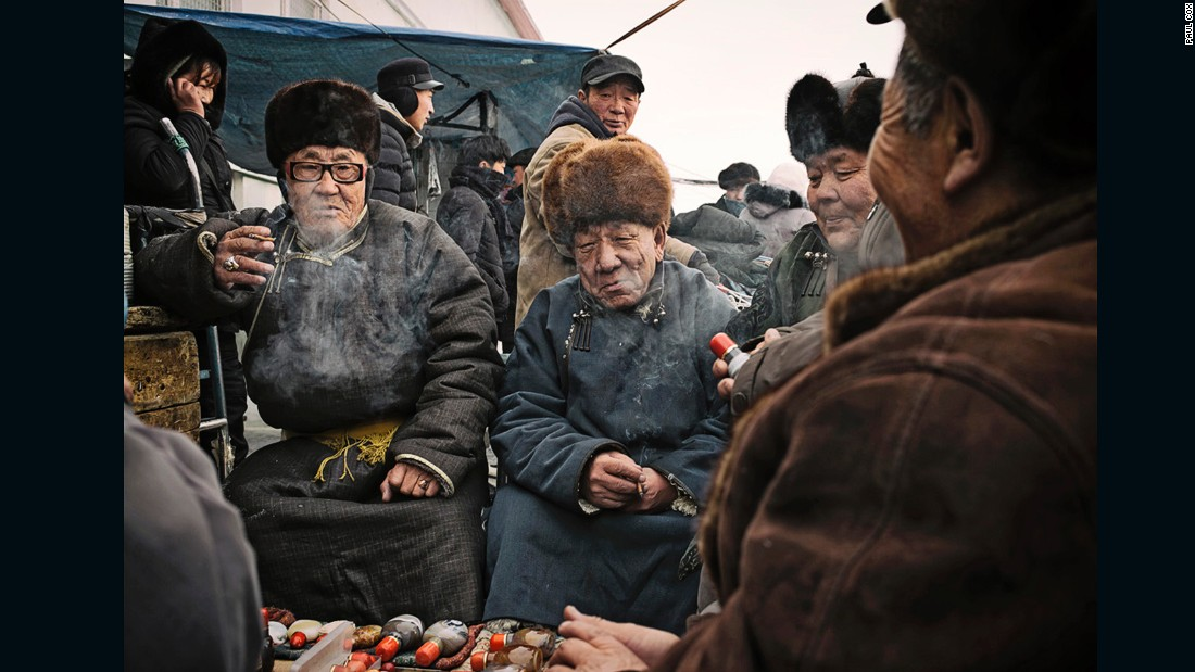 """Locals smoke cigars in an Ulaanbaatar market."""