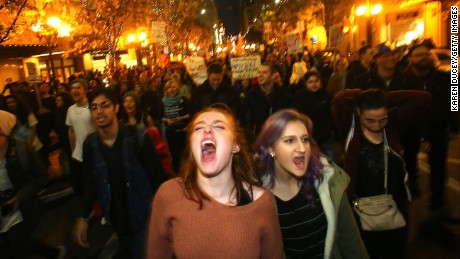 Sasha Savenko and Sydney Kane join thousands of protesters march down 2nd Avenue on November 9 in Seattle, Washington.