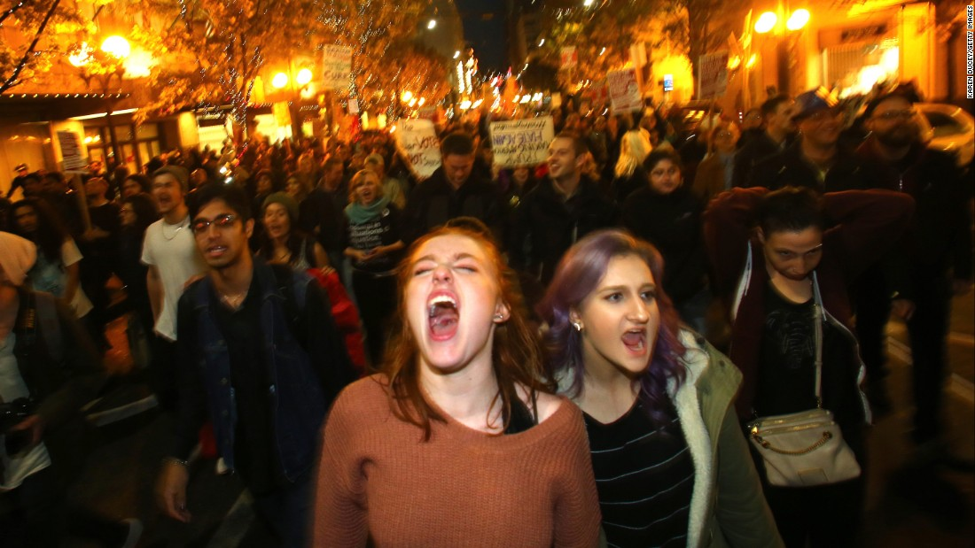 Sasha Savenko, left, and Sydney Kane join thousands of protesters in Seattle on November 9.